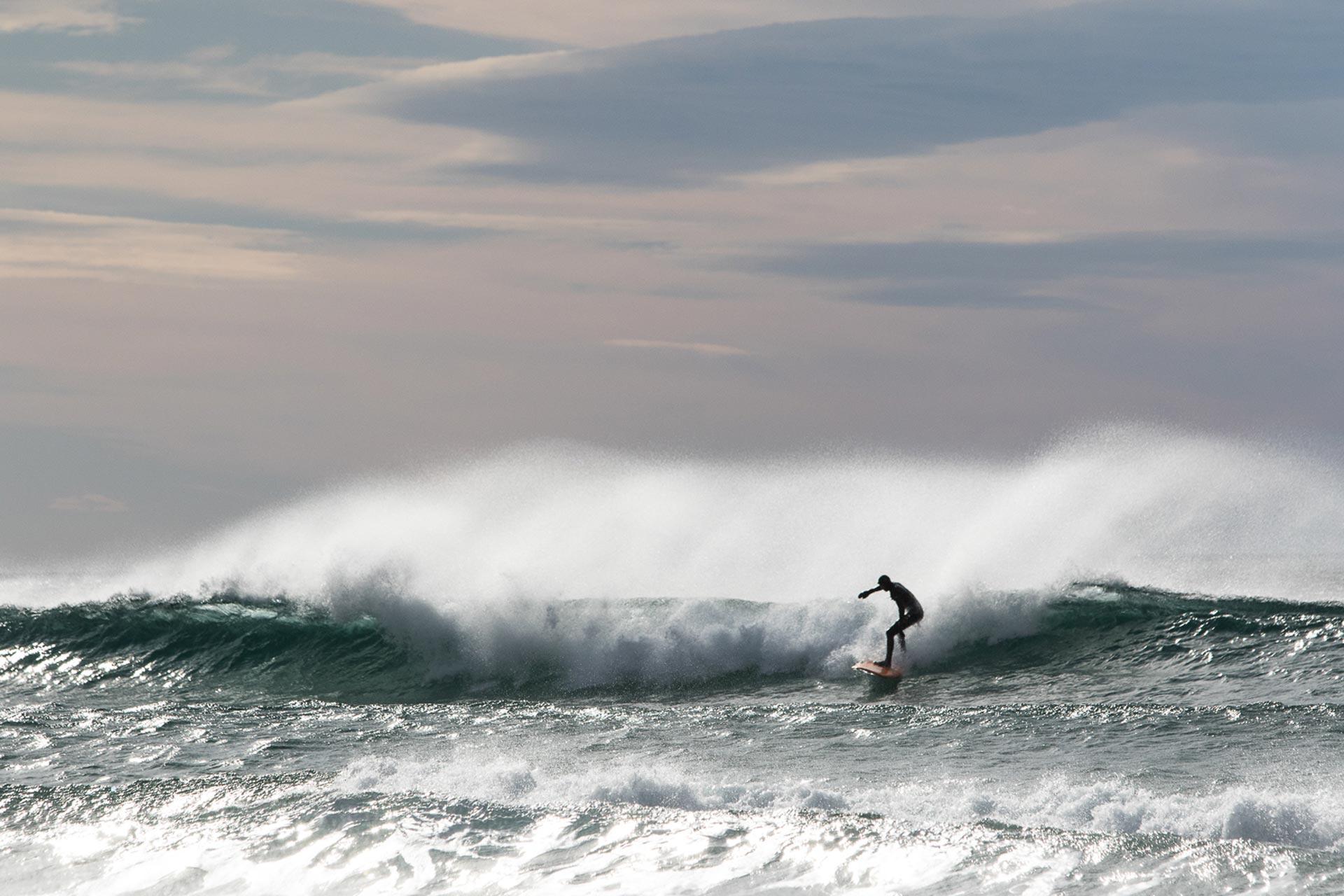 Wenn Schnee und Meer schon so nahe aneinander liegen, muss man die Gelegenheit natürlich auch gleich für ein paar Turns mit dem Surfbrett nutzen. - Foto: Hans-Martin Kudlinski
