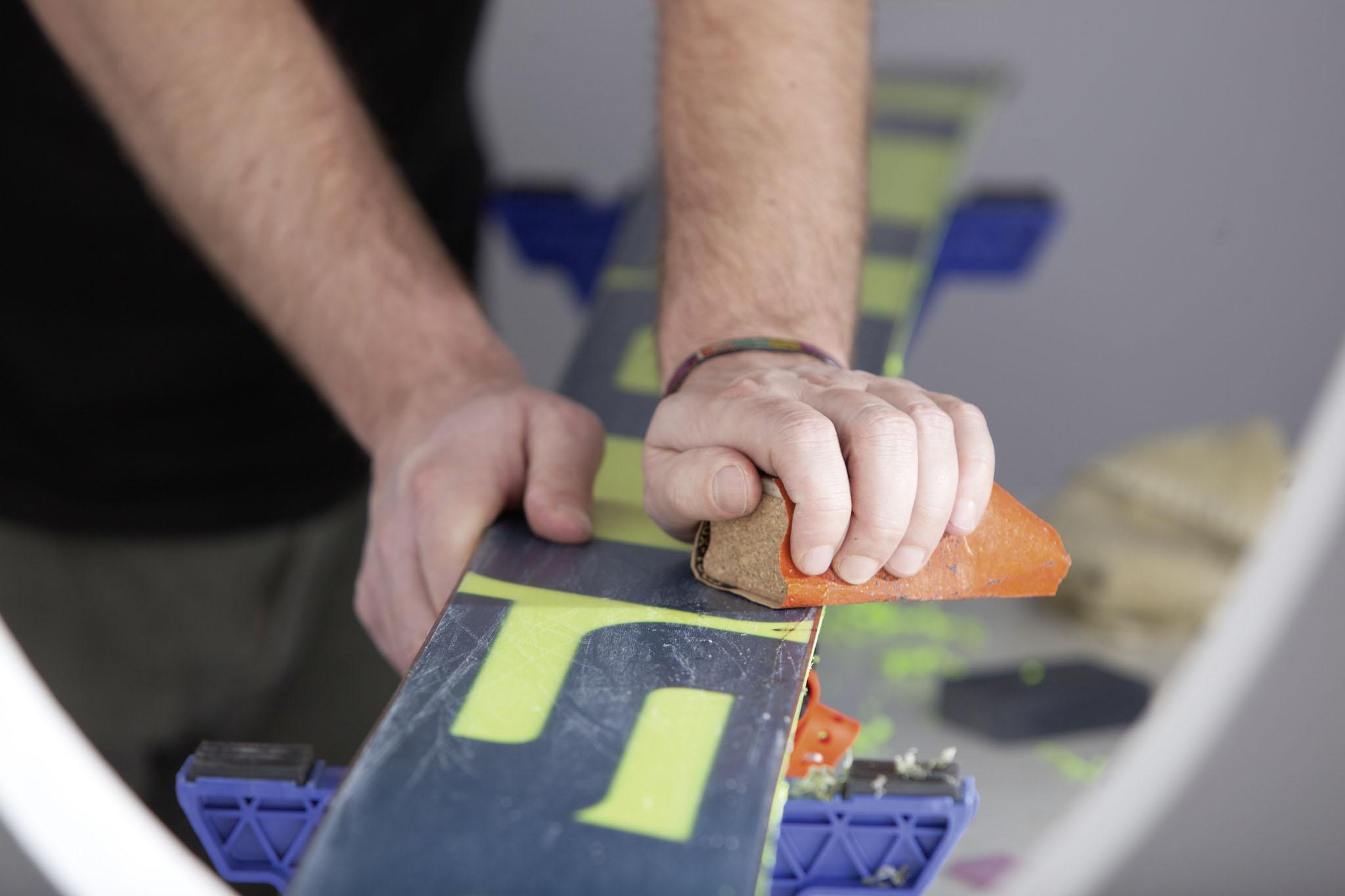 Der letzte Schritt vor dem eigentlichen Wachsen: Mit dem Einsatz von Schleifpapier beseitigt ihr kleinere Kratzer und sorgt gleichzeitig dafür, dass das Wachs einfacher in die Poren des Skis fließen kann.
